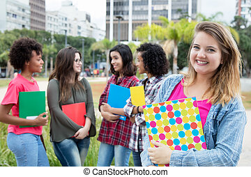 Caucasian female student with group of international...