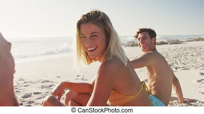 Caucasian friends talking at beach - Front view of multi-...
