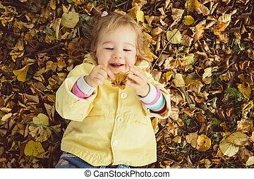 Caucasian girl child lies on the ground and holds an autumn leaf in her hands