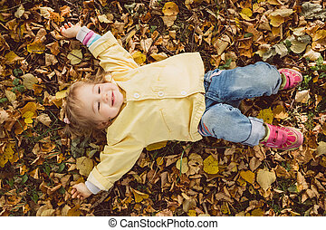 Caucasian girl child lies on the ground and smiles happily among the leaves