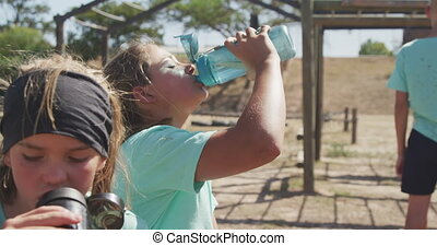 Caucasian girl drinking water at boot camp - Side view of a ...