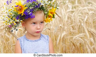 Caucasian girl in a field of flowers. A child in a field in the countryside. Portrait of a girl close up.