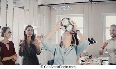 Caucasian girl juggles football on head in office. Happy...