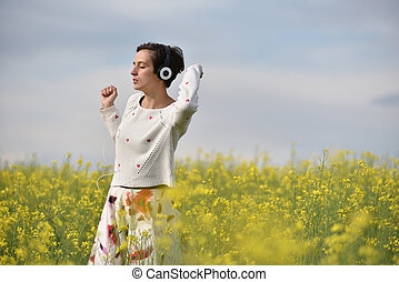 Caucasian girl listening to music with headphone in the outdoors
