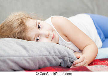 Caucasian girl lying on a pillow and looking at the camera
