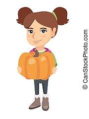 Caucasian girl standing with a big orange pumpkin.