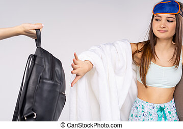 Caucasian girl student, in pajamas and a blindfold refuses a backpack. Weekend. White background.