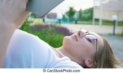 Caucasian girl student lying reading a book outdoors