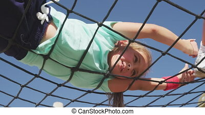 Low angle view of a Caucasian girl having a good time on a boot camp on a sunny day, rolling on a net in the air on a pergola, in slow motion