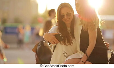 Caucasian girls making selfie background soft sunset light. Young tourist friends enjoy weekend outdoors smiling happy.