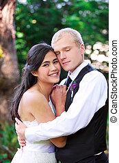 Caucasian groom holding his biracial bride, smiling. Diverse...