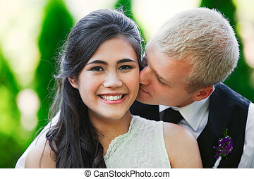 Caucasian groom lovingly kissing his biracial bride on cheek...