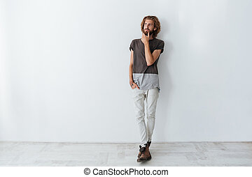 Caucasian handsome man standing isolated over grey wall