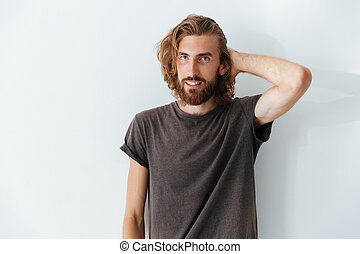 Caucasian handsome man standing isolated over grey wall.
