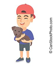 Caucasian happy boy in a cap holding a dog.