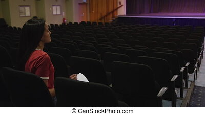 Caucasian high school teenage girl in the auditorium ...