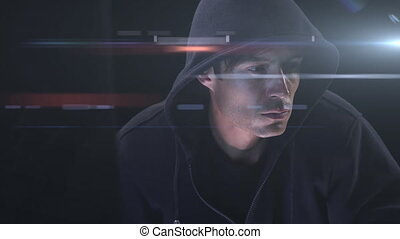 Caucasian hooded hacker man with a laptop ober rays glowing...