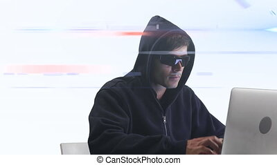 Caucasian hooded hacker man with a laptop over rays glowing...