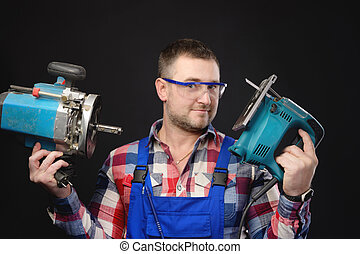 Caucasian joy man builder carpenter in a shirt and overalls with an electric tool in his hands. Studio portrait of friendly artisan businessman