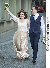 Caucasian Just Married Couple Running on Street Barefoot With Flowers Bouquet.