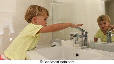 Caucasian kid boy turning tap off in the bathroom