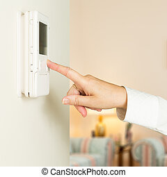 Caucasian lady pressing modern thermostat - Caucasian female...