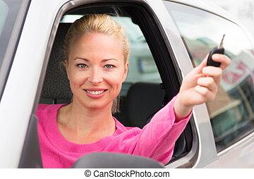 Caucasian lady showing a car key.