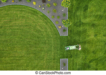 Landscaping Worker Trimming Backyard Grass Using Electric Mower