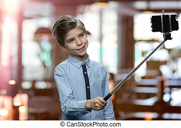 Caucasian little boy is posing for selfie.