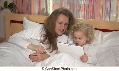 caucasian little girl and mother with tablet computer on bed