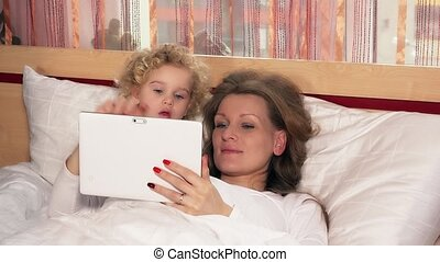 caucasian little girl and mother woman with tablet computer...