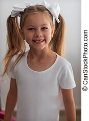 Caucasian long-haired little girl with big white bows on the head . She smiles at the camera