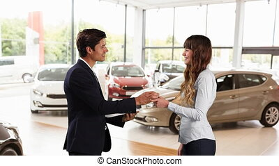 Caucasian male and female shaking hands in a car distributor...