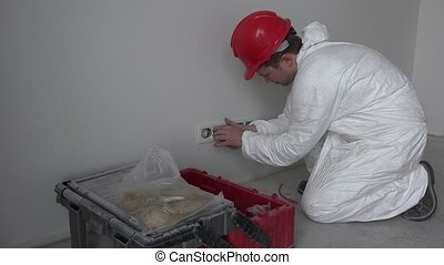 caucasian male electrician mounting socket outlet wall mount in new building