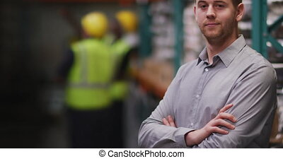 Caucasian male factory worker at a factory looking and ...