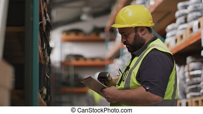 Caucasian male factory worker at a factory wearing a hard ...