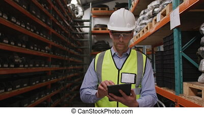 Caucasian male factory worker at a factory wearing a high vis vest using a tablet computer