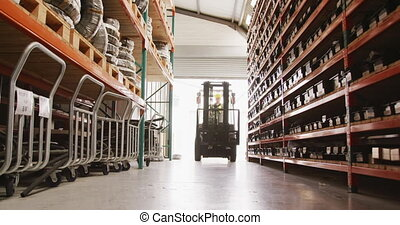 A Caucasian male factory worker at a factory making hydraulic equipment, wearing a hard hat and high vis vest, driving a forklift track in a warehouse storage area, in slow motion.