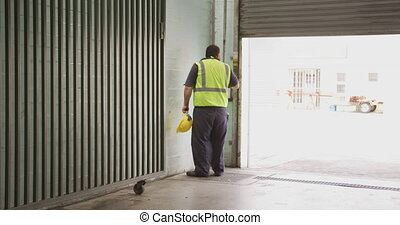 Rare view of a a Caucasian male factory worker at a factory making hydraulic equipment, wearing a high vis vest, holding in hand hard hat, closing a warehouse doors, in slow motion.