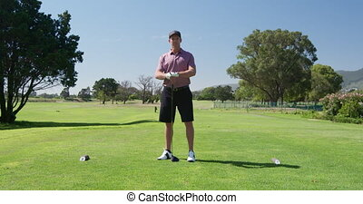 Caucasian male golfer smiling at camera on a golf course - ...