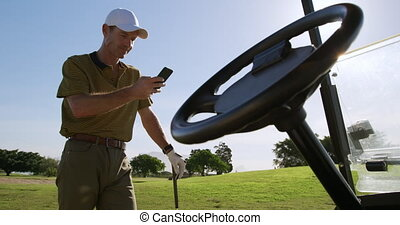 Caucasian male golfer using his smartphone on a golf course...
