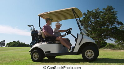 Caucasian male golfers into a golf buggy - Two Caucasian ...