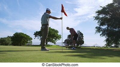 Caucasian male golfers playing on a golf course on a sunny ...