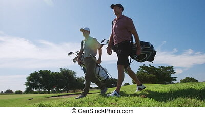 Caucasian male golfers standing on a golf course on a sunny ...