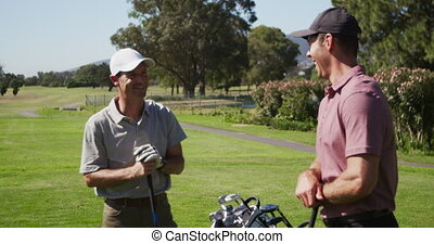 Caucasian male golfers talking on a golf course on a sunny ...