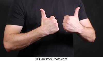 Caucasian male hands in a black short-sleeved T-shirt, pulling two fists with a finger raised up, making an approving gesture on a black background, closeup isolated. High quality FullHD footage