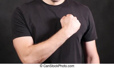 Caucasian male hands in a black short-sleeved T-shirt, beats his chest with his fist on a black background, isolated close-up. High quality FullHD footage