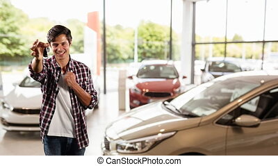 Caucasian male showing his cars keys in a car distributor, ...