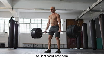 Caucasian male trainer working out with barbell at the gym. sports. training and fitness concept