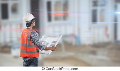 Caucasian male worker wearing an orange high vest and a hat, holding and checking a plan
